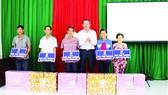 Ông Lưu Hoàng Tân - Chủ tịch, Giám đốc Công ty TNHH MTV Xổ số kiến thiết Đồng Tháp trao bảng tượng trưng  và quà cho 5 hộ nghèo