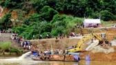 Các cơ quan chức năng tỉnh Tuyên Quang đang phối hợp với chủ đầu tư và đơn vị thi công bơm nước tìm kiếm nạn nhân. Ảnh: TTXVN