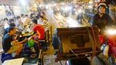 在舊邑郡范文同街上,街頭賣唱者使用大功率擴音器播放以招徠 路人關注。