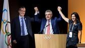 國際奧委會主席巴赫站在中間高舉兩國代表的手表示慶祝。(圖源:互聯網)
