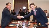 韓國土交通部第二次官金正烈(右)和朝鐵道省副相金潤革握手。(圖源:韓聯社)