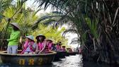 遊客乘坐小圓舟觀光水椰林。