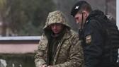 28日,在克里米亞辛菲羅波爾,一名烏克蘭人(左)在警衛護送下離開法庭。(圖源:AFP)