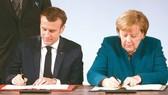 德國總理默克爾(右)和法國總統馬克龍(左)當地時間22日在德國西部城市亞琛簽署《德國和法國關於合作和一體化的條約》(《亞琛條約》)。(圖源:AFP)