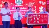 芽莊啟明華文中心董事長鄭成龍(右一)向 萬盛發集團代表麒麟(左三)和本市各華人會館贈送感謝金牌。