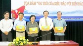 Mr. Hoang Chi Hung (L), chairman of the Press Photo Club under HCMC Journalists Association gives delegates at the seminar photobooks on sea and islands (Photo: SGGP)