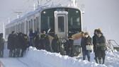 Hành khách ra khỏi xe lửa sáng 12-1-2018 sau khi phải qua đêm trên đoàn xe lửa bị mắc kẹt do tuyết rơi dày ở TP Sanjo, tỉnh Niigata, Nhật Bản. Ảnh: KYODO