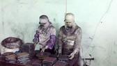 Công nhân trong cơ sở của bà Chúc đang dùng bột than tre đóng vào viên con nhộng để làm thuốc chữa ung thư