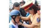 Tuyên truyền, tặng nón bảo hiểm cho học sinh đến trường