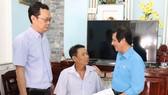Chủ tịch Công đoàn Sawaco  Tô Trung Dũng (bìa phải) và  Giám đốc Nhà máy nước Thủ Đức Phạm Tuấn Anh (bìa trái)  trao tiền đến anh Nguyễn Anh Tuấn