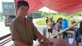 Ông Nguyễn Tiến Phừng bên các bẫy dính đầy ruồi tại cổng nhà máy xử lý rác thải để phản ánh tình trạng ô nhiễm