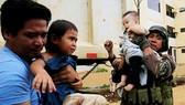 Bùng phát giao tranh giữa quân chính phủ và lực lượng phiến quân là một trong những nguyên nhân khiến Tổng thống Philippines Rodrigo Duterte đuối sức. Hình ảnh binh sĩ Philippines và nhân viên cứu hộ giải cứu hai trẻ em ở Marawi. Ảnh: REUTERS
