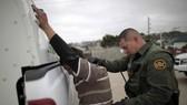 Lực lượng an ninh bắt giữ người nhập cư bất hợp pháp vào Mỹ. Ảnh: REUTERS