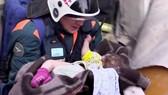 Các nhân viên cứu hộ đưa bé trai ra khỏi đống đổ nát. Nguồn: NBC NEWS
