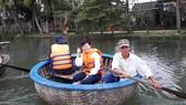 Nông dân chèo thuyền thúng đưa khách tham quan sông Cổ Cò. Ảnh: TRUNG CHÂU
