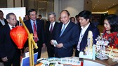Thủ tướng  Nguyễn Xuân Phúc và các đại biểu thăm gian hàng  trưng bày  tại hội nghị.  Ảnh: TTXVN