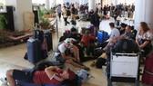 Các du khách nước ngoài ngồi, nằm la liệt ở sân bay quốc tế Lambok sau trận động đất ngày 6-8. Ảnh: REUTERS