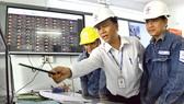Kỹ sư Đỗ Tiến Trung (giữa) và đồng nghiệp giám sát hệ thống lưới điện  tại Trung tâm quản lý lưới điện Hóc Môn