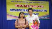 Tác giả trẻ Trương Chí Hùng nhận giải nhất cuộc thi Bút ký ĐBSCL năm 2018, bên cạnh là nhà văn Nguyễn Ngọc Tư. Ảnh: QUỐC TUẤN