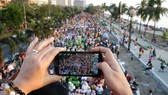A person uses her cellphone to photo the procession by thousands of devotees to celebrate the feast day of the Child Jesus in Manila, Philippines. A consortium led by the parent of China Telecom has been granted a license to run the Philippines' third tel