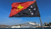The national flag of Papua New Guinea flies in front of boats berthed in Port Moresby. China's Huawei has won a bid to build the country's telecommunications network.   © Getty Images