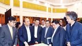 Thủ tướng Nguyễn Xuân Phúc và các đại biểu xem mô hình Trung tâm đổi mới sáng tạo quốc gia Ảnh: TTXVN