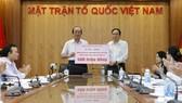 Bộ trưởng, Chủ nhiệm Văn phòng Chính phủ Mai Tiến Dũng thay mặt Chính phủ chuyển 400 triệu đồng đến Ủy ban Trung ương MTTQ Việt Nam để ủng hộ các tỉnh miền núi phía Bắc khắc phục thiệt hại do mưa lũ. Ảnh: TTXVN