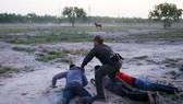 Một nhân viên tuần tra biên giới của Mỹ khống chế 3 người vượt biên trái phép. Ảnh: REUTERS