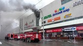 This handout picture released by the Russian Emergency Situations Ministry shows emergency vehicles as they gather outside a burning shopping centre in Kemerovo, in western Siberia. — AFP/VNA Photo