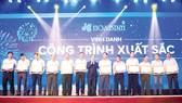Ông Lê Viết Hải - Chủ tịch HĐQT kiêm Tổng Giám đốc Tập đoàn Xây dựng Hòa Bình (chính giữa) trao thưởng cho tập thể, cá nhân xuất sắc