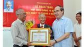 Bí thư Thành ủy TPHCM Nguyễn Thiện Nhân trao Huy hiệu 70 năm tuổi Đảng cho đồng chí Lê Văn Nghị. Ảnh: VIỆT DŨNG