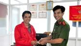 Thiếu úy Văn Ngọc Cường trao lại tiền và giấy tờ cho anh Hoàng Trọng Hiếu