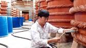 Kiểm tra chất lượng nước mắm trong quá trình rút kéo nước mắm bên trong nhà thùng tại Phú Quốc       Ảnh: NGỌC CHÁNH