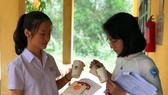 Duyên và Thúy giới thiệu các sản phẩm thân thiện môi trường do 2 em sáng chế từ bã mía và vỏ tôm, cua