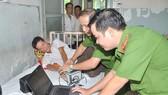 Trung tá Nguyễn Văn Trường (phải) cùng đồng nghiệp đến  Bệnh viện Ung Bướu, quận Bình Thạnh làm thẻ căn cước cho ông Nguyễn Hữu Nghĩa