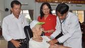 Đoàn Từ thiện Hội Chữ thập Đỏ bệnh viện Hùng Vương khám bệnh cho người già khuyết tật xã Kim Long. Ảnh: Hồng Huê - Quang Việt