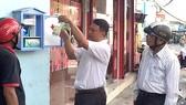 Cán bộ Hội Chữ thập đỏ hướng dẫn cho người dân  xung quanh sử dụng tủ thuốc sơ cấp cứu.