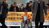 Cụ bà Kim Seong-ju, một trong những nạn nhân được yêu cầu bồi thường,ngồi chờ phán quyết bên ngoài Tòa án ngày 29-11 (Ảnh : Reuters)