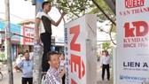 Người dân buôn bán trên đường Nguyễn Thị Thập, quận 7 tự nguyện tháo dỡ bảng quảng cáo lấn chiếm vỉa hè, vào đầu tháng 3-2017. Ảnh: Việt Dũng