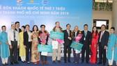 Phó Chủ tịch thường trực UBND TPHCM Lê Thanh Liêm và ông Bùi Tá Hoàng Vũ, Giám đốc Sở Du lịch TPHCM chụp ảnh lưu niệm cùng 3 vị khách đặc biệt trong năm 2018.