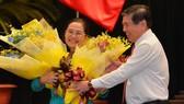 Chủ tịch UBND TPHCM Nguyễn Thành Phong tặng hoa chúc mừng đồng chí Nguyễn Thị Lệ. Ảnh: VIỆT DŨNG