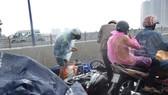 Người dân lưu thông trên cầu té ngã vì đường trơn trượt trong cơn mưa lớn. Ảnh: C.T