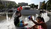 兒童在噴泉戲水解暑。(圖片來源:中新網)