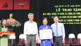 第五郡領導向華人黨員李金梅 頒贈50年黨齡紀念章。