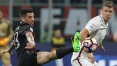 Edin Dzeko (phải, Roma) tranh bóng với hậu vệ Jose Sosa (Milan). Ảnh: Getty Images.