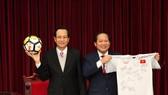 Bộ trưởng Bộ LĐ-TB&XH Đào Ngọc Dung (trái) và Bộ trưởng Bộ Thông tin và Truyền thông Trương Minh Tuấn nhận trái bóng, chiếc áo đấu của U23 Việt Nam tặng Thủ tướng Chính phủ để chuẩn bị đấu giá. Nguồn: VGP