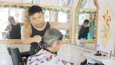 Anh Lê Minh Tân đang cắt tóc miễn phí cho một cụ già neo đơn