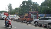 Phương tiện giao thông nối đuôi nhau chạy ngang qua cổng Trường THPT Lương Văn Can, quận 8, TPHCM. Ảnh: THÀNH TRÍ