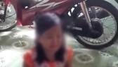 Bé gái 10 tuổi đang kể vụ việc với một người phụ nữ. Ảnh cắt từ clip