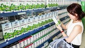 A consumer shops for milk products of the national dairy company Vinamilk. (Photo: VNA)